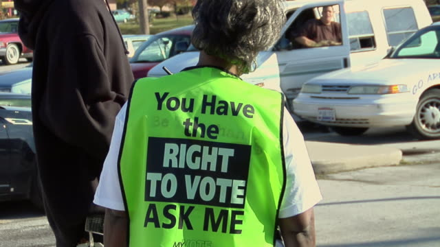 MS, ZO, Election worker wearing fluorescent vest talking to man outside polling place, Toledo, Ohio, USA