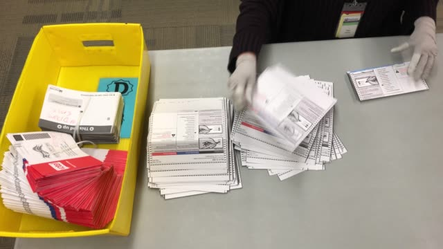 stockvideo's en b-roll-footage met election worker wearing protective gloves sort through mailed-in ballots at the king county elections ballot processing center on march 09, 2020 in... - staat washington