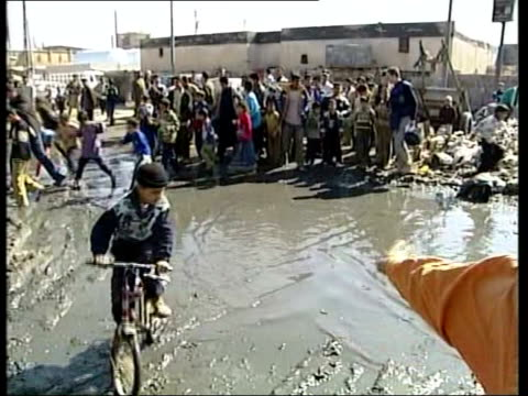 basra build up; iraq: basra: ext young boy pushing cart through muddy neglected street in poorest part of basra woman towards man along and past on... - basra video stock e b–roll