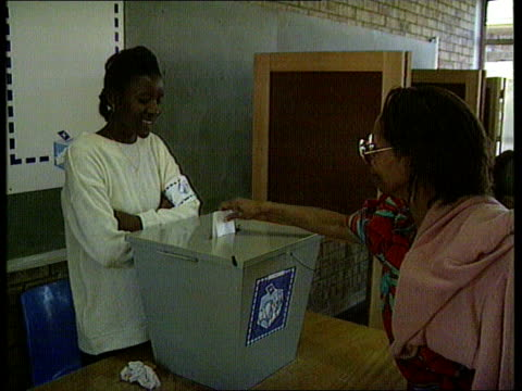 stockvideo's en b-roll-footage met elections itn gv queue at polling station with sun rising ms ditto black woman putting vote in ballot box cms black man intvwd sot here we are in the... - 1994