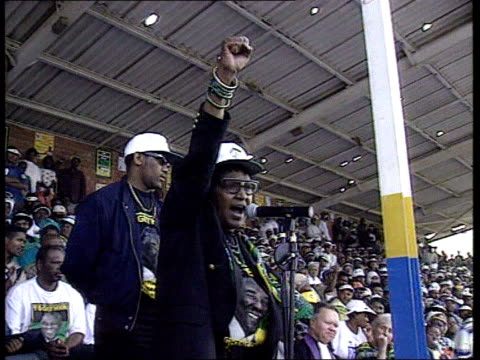 Elections Mandela standing down ITN EXT Winnie Mandela addressing rally ANC supporters at rally with flag Mandela addressing rally