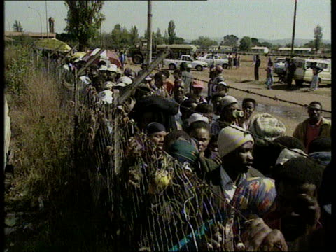 stockvideo's en b-roll-footage met elections south africa / politics elections s africa airv vast queue of people in field as they wait to vote katlehong tcms people queueing at... - 1994