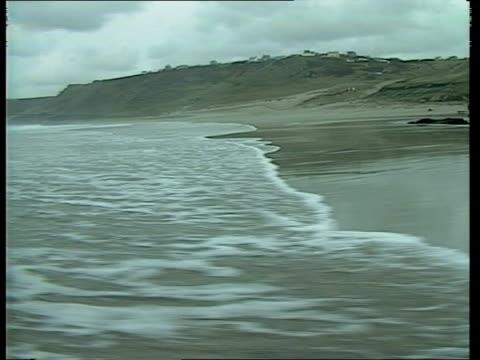 water issue b england cornwall tms waves lapping onto beach ms beachside houses - アルファベットのb点の映像素材/bロール