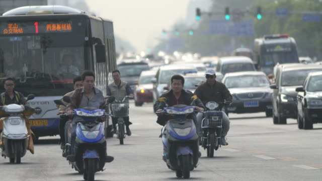Electric bicycle riders in rush hour traffic in Beijing, China