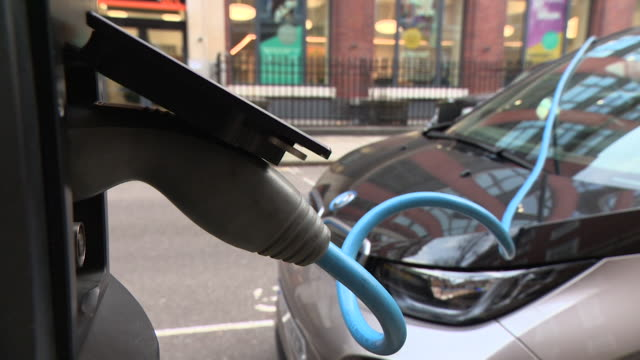 bmw electric car being charged at charging station in a london street - bmw stock videos & royalty-free footage