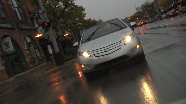 stockvideo's en b-roll-footage met ws pov electric car being driven in city traffic in rain / rochester, michigan, united states - hybride voertuig