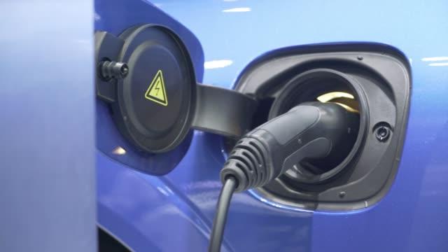 vídeos de stock, filmes e b-roll de combustível de carregamento do carro elétrico na estação da geração de energia - posto de carregamento de veículos elétricos