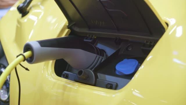 vídeos y material grabado en eventos de stock de coche eléctrico cargando combustible en la estación de generación de energía - coche híbrido