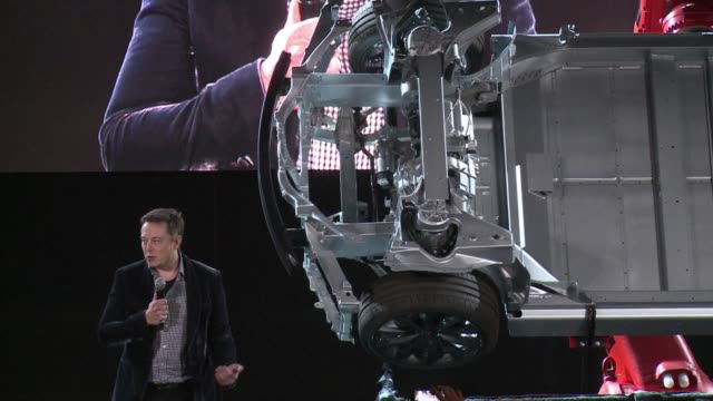vídeos de stock, filmes e b-roll de electric car giant tesla unveils a new two engine vehicle designed to perform in bad weather featuring four wheel drive and anti collision technology - festa de lançamento