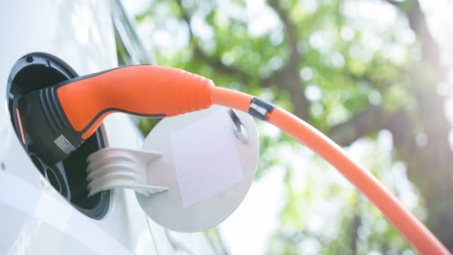 Electric car plugged in charging in the suburbs under green trees
