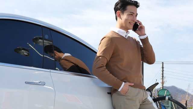 electric car - young man talking on his smart phone and leaning against his car while charging it - moving image stock videos & royalty-free footage