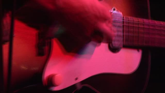 CU Electric guitar being strummed under red stage light/ Austin, Texas