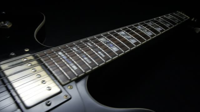 electric guitar on black background. tracking shot - single object stock videos & royalty-free footage