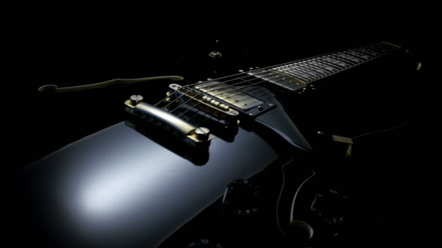 electric guitar on black background. tracking shot - electric guitar stock videos and b-roll footage