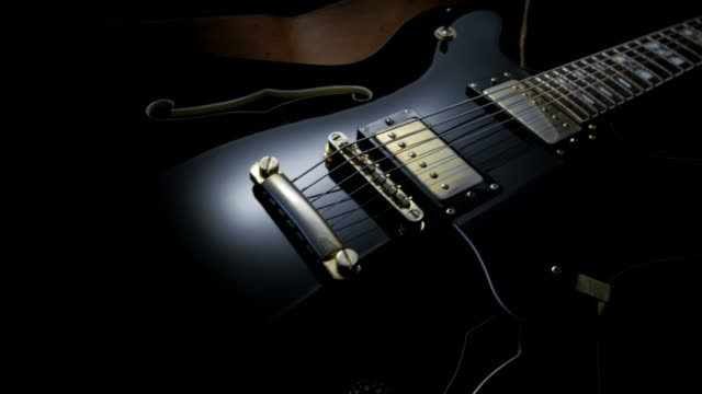 electric guitar on black background. tracking shot - rock object stock videos & royalty-free footage