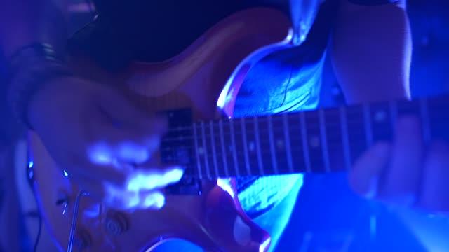 vídeos de stock, filmes e b-roll de jogador de guitarra elétrica em um estágio com iluminação cénico azul colorida - violão