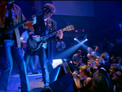 stockvideo's en b-roll-footage met 2 electric guitarists playing in rock concert near edge of stage by fans - moderne rock