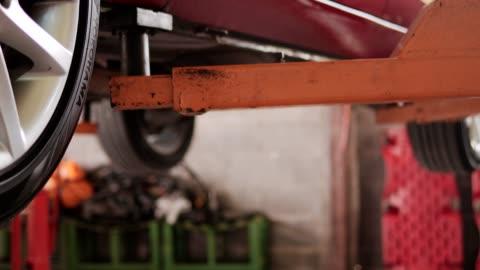 electric hoist lifting car in garage.4k slow footage - hoisting stock videos & royalty-free footage