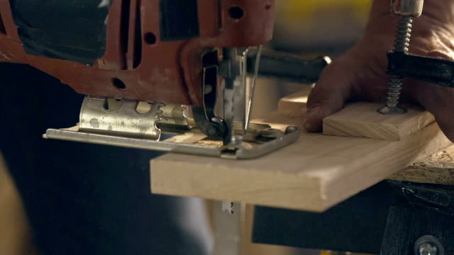 Electric jigsaw sawing piece of wood
