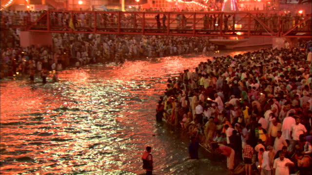 electric lights illuminate the ganges river in haridwar, india, where hundreds of people gather. - india stock videos & royalty-free footage