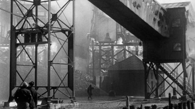 vídeos de stock e filmes b-roll de electric plant structure in flames with men standing close by / fire hoses dampen down smoldering electricity pylon / crowd of men watch as... - general electric