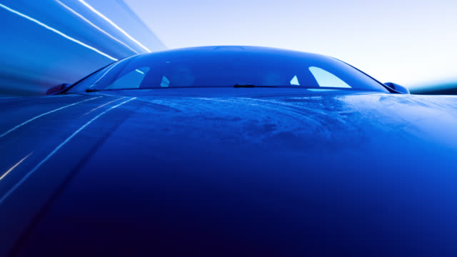 electric powered red car drives on highway and into a city - iced bonnet in the beginning while blue hour. - made in the usa kort fras bildbanksvideor och videomaterial från bakom kulisserna