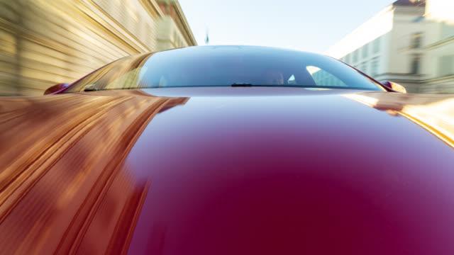 electric powered red e car drives through the city of munich while sunny morning. - made in the usa kort fras bildbanksvideor och videomaterial från bakom kulisserna