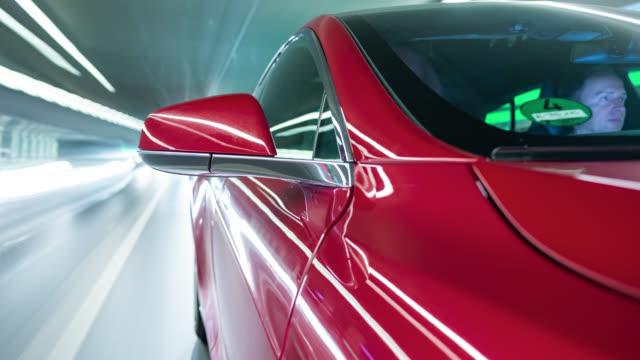 electric powered red e-car drives on city highway and through tunnels in the city of munich. - made in the usa kort fras bildbanksvideor och videomaterial från bakom kulisserna