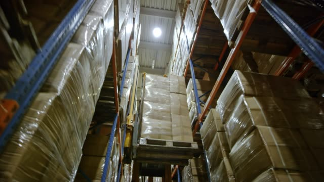 ds electric reach truck driving in warehouse aisle and raising the pallet - packaging stock videos & royalty-free footage