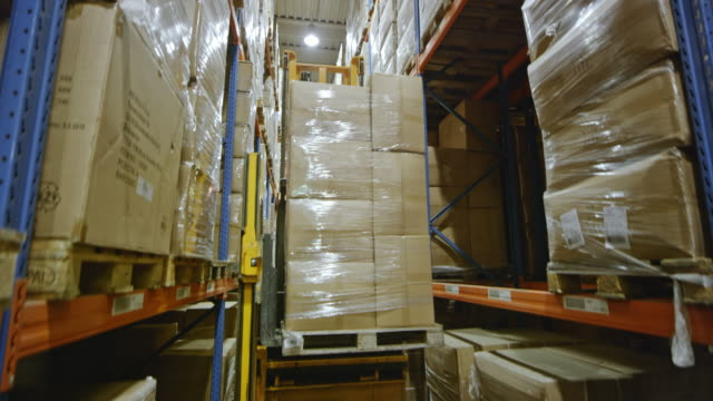 ds electric reach truck raising the pallet sitting on the forks and putting it onto the rack - forklift stock videos & royalty-free footage