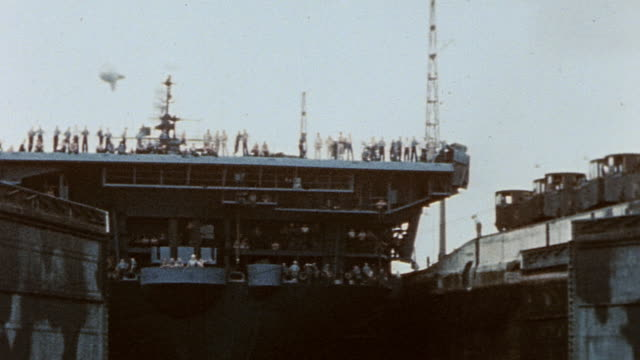 Electric train on tracks after pulling USS Yorktown into canal lock and lock doors closing / Panama