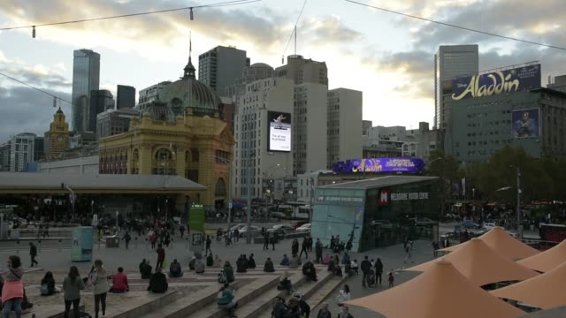Electric trains travel along railway tracks at dusk in Melbourne Australia on Friday April 28 A large screen plays a video on the side of a building...
