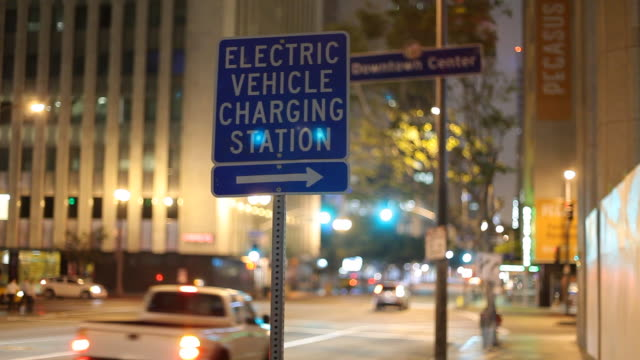 WS Electric vehicles charging station sign on street at night / Los Angeles, California, USA