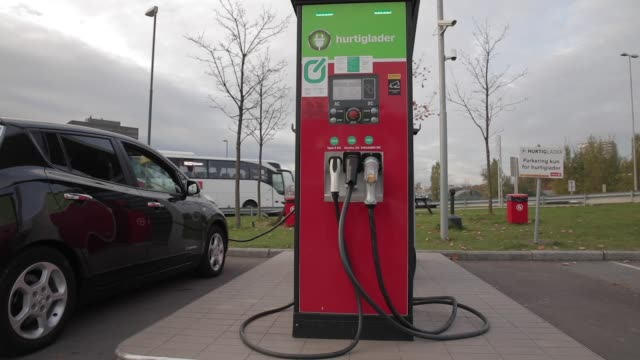 electric vehicles recharge at a charging station near a forecourt of fossil fuel powered automobiles refueling at petrol pumps at a circle k gas... - personal land vehicle stock videos & royalty-free footage