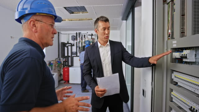 electrical engineer and new home owner shaking hands standing by the large electrical panel - health and safety stock videos & royalty-free footage