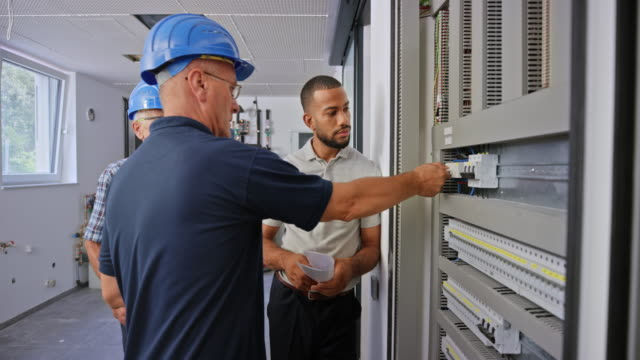 vídeos y material grabado en eventos de stock de ingeniero eléctrico explicando los disyuntores en el panel eléctrico al propietario de la nueva casa - camisa de polo