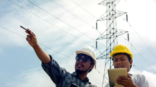 電気エンジニア inspects 、プロジェクトの進行中にデジタルタブレットを持っている - 整備員点の映像素材/bロール