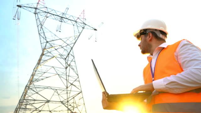 vídeos de stock, filmes e b-roll de engenheiro elétrico é usando laptop - equipamento elétrico equipamento industrial