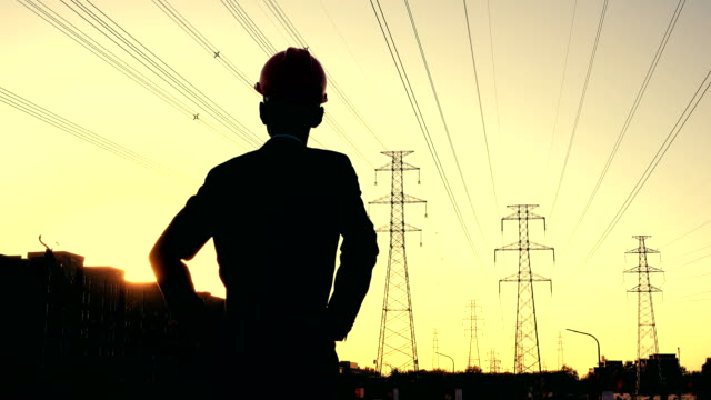 electrical engineer rear view at sunset - electricity pylon stock videos & royalty-free footage