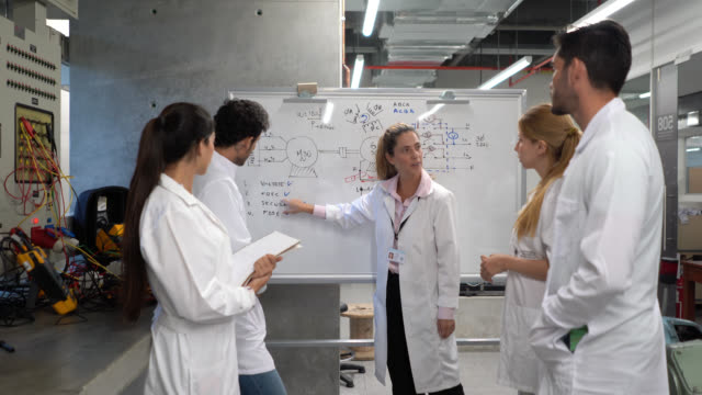 electrical engineer teacher explaining something to students pointing at the white board and electrical board at the laboratory - lab coat stock videos & royalty-free footage