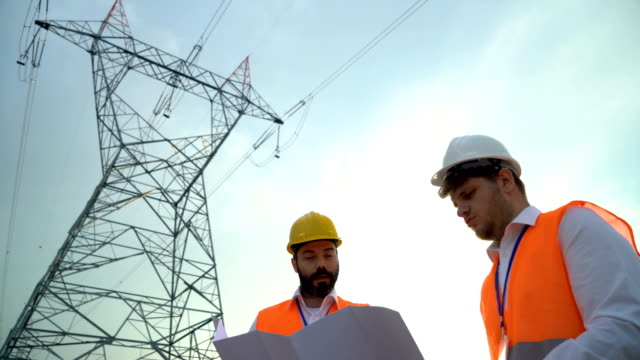stockvideo's en b-roll-footage met electrical engineers werken aan het project - bord hoogspanning
