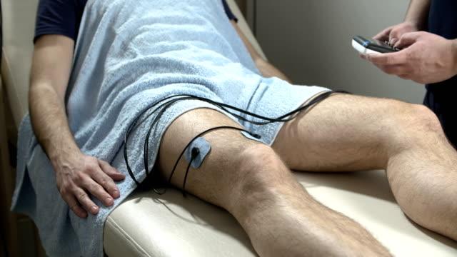 vídeos de stock, filmes e b-roll de terapia de estimulação elétrica do músculo - fisioterapeuta