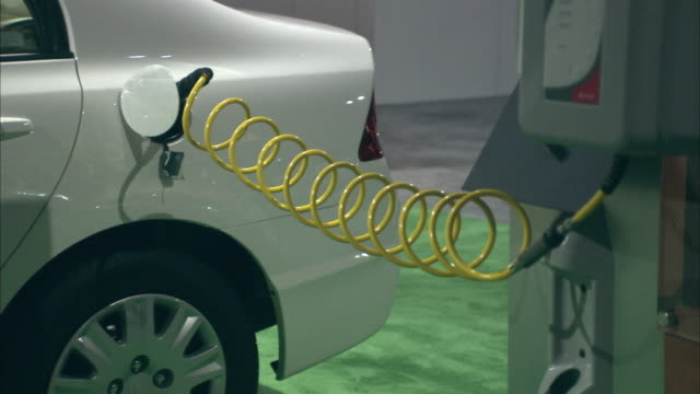 CU, Electrical plug recharging electric car in Los Angeles Auto Show, California, USA