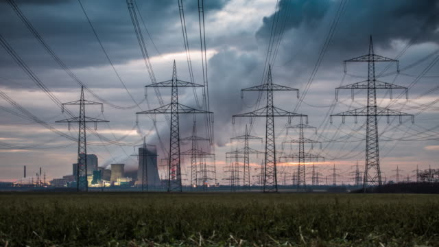 time lapse: electrical pylons in front of a power station - tracking shot - elettricità video stock e b–roll