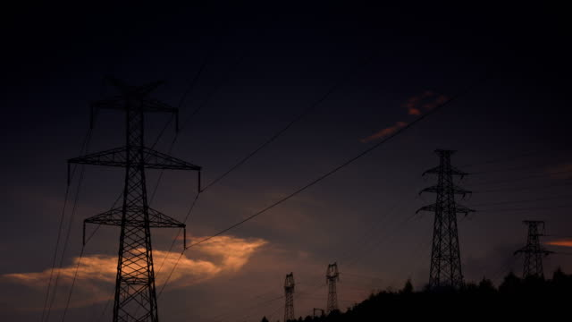 electrical pylons with sunglow 4k video - electricity pylon stock videos & royalty-free footage