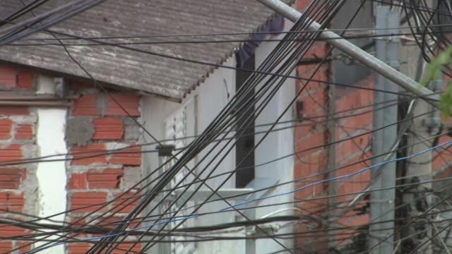 electrical wires crisscross in front of a brick building. - crisscross stock videos & royalty-free footage