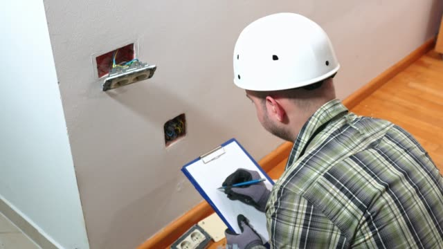 electrician calculating voltage, writing notes - plug socket stock videos & royalty-free footage