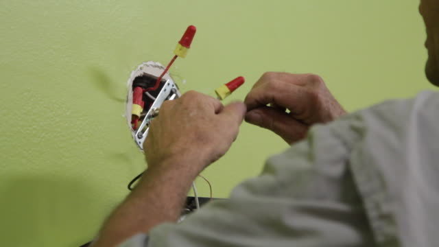 Electrician Connecting New Wires To Wall Fixture