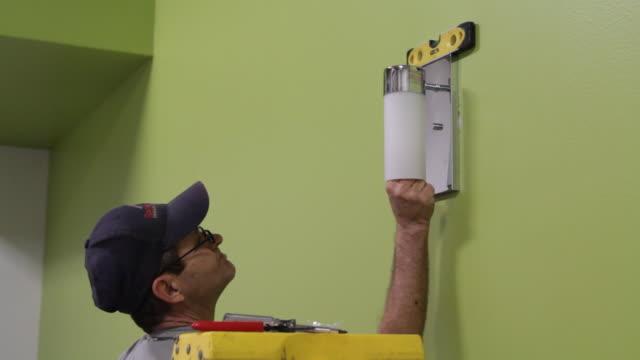 electrician finishing up with new lightbulb fixture - endast en medelålders man bildbanksvideor och videomaterial från bakom kulisserna