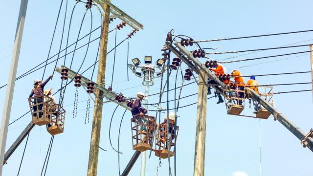 vídeos de stock, filmes e b-roll de eletricista fixação linha de eletricidade - alta voltagem